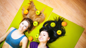 Two young athletic physique women in gym Lie on the floor on yoga mats Stock Photo