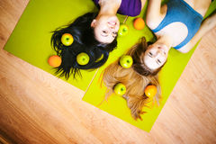 Two young athletic physique women in gym Lie on the floor on yoga mats Royalty Free Stock Images