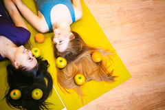 Two young athletic physique women in gym Lie on the floor on yoga mats Royalty Free Stock Photo