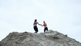 Two young, athletic women doing exercises outdoors, on the sandy top of the quarry. On the beach, cargo port, on the stock footage
