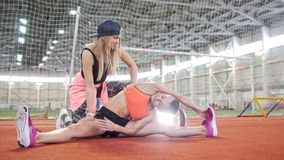 Two young athletic women doing sports. Doing stretching stock video footage