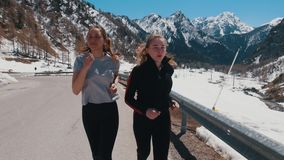 Two young athletic women running down the road on the background of the snowy mountain stock footage