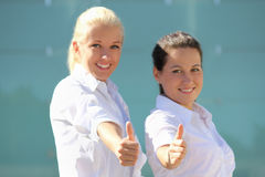Two young attractive business women thumb up. focus on hands Royalty Free Stock Photo