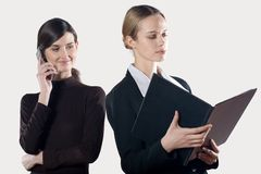Two young attractive businesswomen with cellphone and folder Stock Photo