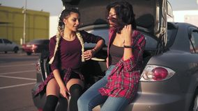 Two young attractive friends sitting in car trunk in the parking by the shopping mall and talking, smiling happily. Slowmotion shot stock video