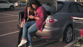 Two young attractive girlfriends sitting inside of the open car trunk in the parking by the shopping mall and talking. Looking at the picture in the smartphone stock video