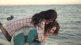 Two young attractive girls have fun and embrace. best friends spend time together outdoors by the water. portrait of stock footage