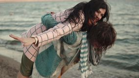 Two young attractive girls have fun and embrace. best friends spend time together outdoors by the water. portrait of. Young woman in elegant coat walks on the stock video