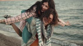 Two young attractive girls have fun and embrace. best friends spend time together outdoors by the water. portrait of. Young woman in elegant coat walks on the stock footage