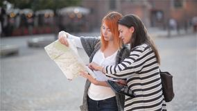 Two young attractive girls are looking aside in the urban zone while exploring the city. Caucasian women are walking. With the paper map to find interesting stock footage