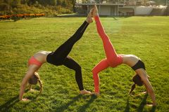 Two young attractive girls practicing yoga outdoor. Two young attractive girls practicing yoga outdoor Stock Photo