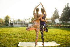Two young attractive girls practicing yoga outdoor. Two young attractive girls practicing yoga outdoor Royalty Free Stock Photography
