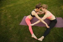 Two young attractive girls practicing yoga outdoor. Two young attractive girls practicing yoga outdoor Stock Photos