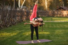 Two young attractive girls practicing yoga outdoor. Two young attractive girls practicing yoga outdoor Stock Photography