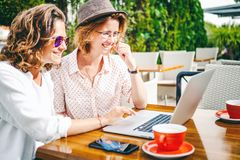 Two young attractive girls are sitting in a cafe with coffee and. A laptop, internet and shopping onine, communication and friendship Royalty Free Stock Photos