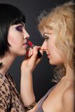 Two young attractive lesbians are hugging with a lipstick Stock Photos