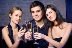 Two young attractive sweet women and man with champagne glasses. At a night party royalty free stock image