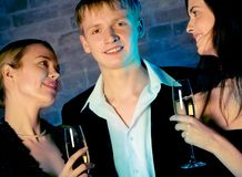 Two young attractive sweet women and man with champagne glasses Stock Photos