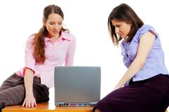Two young attractive women with a computer. Two young attractive women working with the computer Stock Photography