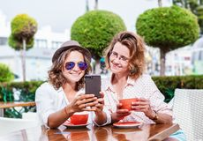 Two young attractive women girlfriends girls are sitting in a ca. Fe, talking, doing online shopping, drinking coffee and looking at the mobile phone Stock Photography