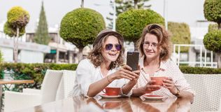 Two young attractive women girlfriends girls are sitting in a ca. Fe, talking, doing online shopping, drinking coffee and looking at the mobile phone Stock Image