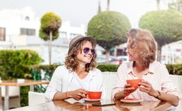 Two young attractive women girlfriends girls are sitting in a ca. Fe, chatting with a cup of coffee, friendship, communication, travel and vacations Stock Photos
