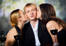 Two young attractive women kissing man with red-wine glasse. Two young attractive sweet women kissing man with red-wine glasses at the celebration or party Royalty Free Stock Photography