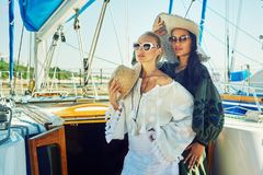 Two young attractive women are resting on a yacht on a Sunny day royalty free stock photo
