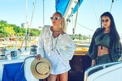Two young attractive women are resting on a yacht on a Sunny day stock image