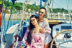 Two young attractive women are resting on a yacht on a Sunny day royalty free stock photography