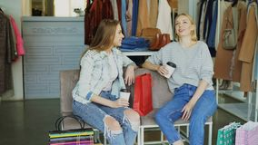 Two young women sitting on leather-covered chairs in clothes boutique and chatting after shopping . Nice modern women`s. Two young attractive women sitting on stock video