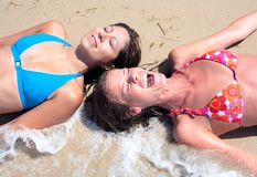 Two young attractive women splashed by cold wave on the beach royalty free stock image