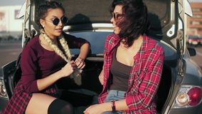 Two young attractive women in stylish sunglasses sitting in car trunk in the parking by the shopping mall and talking. During sunny day. Slowmotion shot stock video