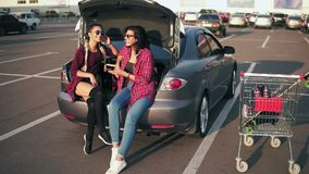 Two young attractive women in sunglasses sitting inside of the open car trunk and listening to the music in the. Smartphone. Their shopping cart standing near stock video footage
