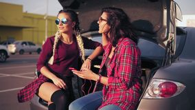 Two young attractive women in sunglasses sitting inside of the open car trunk in the parking by the shopping mall and. Listening to the music in the smartphone stock video footage