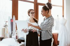 Two young attractive women working on new design project.  royalty free stock photos