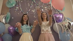 Two young attractive excited women in fancy pretty dresses with air balloons throwing confetti glitter smiling in camera. Two young attractiveexcited women in stock video