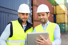 Two young attractives dockers working on the dock Stock Photos