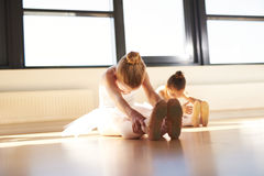 Two Young Ballerinas Exercising Inside the Studio. Two Young Ballerinas Doing an Exercise, Especially for their Legs, Inside the Studio Before the Actual Dance Royalty Free Stock Images