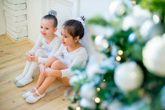 Two young ballet dancer sitting near Christmas tree. On the wooden floor and smile Stock Image