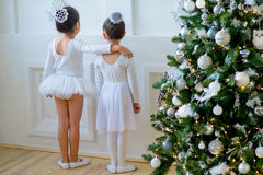 Two young ballet dancers learning the lesson near Christmas tree. Try some new pose Stock Photos