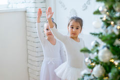Two young ballet dancers learning the lesson near Christmas tree. Try some new pose Stock Images