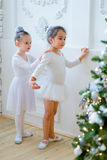 Two young ballet dancers learning the lesson near Christmas tree. Try some new pose Stock Image
