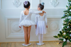 Two young ballet dancers learning the lesson near Christmas tree. Try some new pose Royalty Free Stock Photos