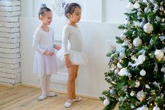 Two young ballet dancers learning the lesson near Christmas tree. Try some new pose Royalty Free Stock Photography