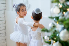 Two young ballet dancers learning the lesson near Christmas tree. Try some new pose Stock Photo
