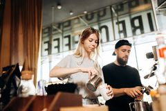 Two young baristas,a blonde girl and stylish man with beard,are shown cooking coffee together in a coffee machine in a royalty free stock photography