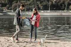 Two young beaming students standing near the river while cleaning the sand. Cleaning sand. Two young beaming students standing near the river while feeling royalty free stock photography
