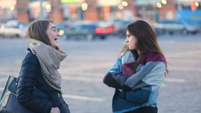 Two young beatiful pretty student stylish girls talking and laughing on the urban street near the cars, Steady cam, slow. Two young beatiful pretty student stock video footage
