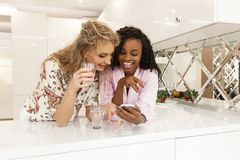 Two young beautiful african and caucasian girl friends laughing while looking at the mobile screen. royalty free stock images